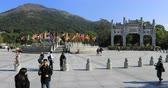 fiel : Hong Kong, China - December 11, 2016: believer people and Buddhist monks at gateway of Po Lin Monastery of Big Buddha on background, symbol of Lantau Island, popular tourist destination. Time lapse