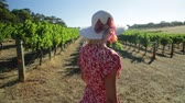 маргарита : Australian woman farmer portrait, walks among the rows of white grapes. Blonde in red dress and hat getting ready for harvest. Sunset light. Margaret River, Western Australia. close up.