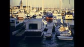 pescador : San Francisco, California, United States - in 1980: Archival 80s footage about boats and yachts docked at Pier 39 of Fishermans Wharf at sunset.