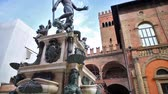 emilia : Bologna, Italy - March 12, 2018:Bologna Neptune fountain of Bologna city. Restored Nettuno bronze statue, with historic orange-red tower buildings background in Nettuno square of Bologna city center.