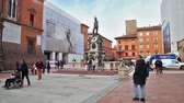 emilia : Bologna, Italy - March 12, 2018:Nettuno 1567 bronze statue and fountain in front of Accursio palace, built in 1290, in Piazza Maggiore square, the seat of the municipal government of Bologna city. Stock Footage
