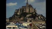 brittany : Mont Saint-Michel, FRANCE - July 12,1976: ground panorama with tourists in the car parking of Historic Saint Michaels Mount in the 70s. People in vintage 1970s dress and vintage cars and bus. Stock Footage