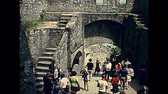brittany : Mont Saint-Michel, FRANCE - July 12,1976: Tourists at entrance town hall of Historic abbey monastery in Mont Saint-Michel in 70s. Saint Michaels Mount, France 1970s archival UNESCO Heritage. Stock Footage