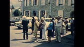 vezetett : Saint-Thegonnec, Morlaix, Brittany, FRANCE - July 15, 1976: vintage dressed tourists in the park of Notre-Dame church at Saint-Thegonnec parish for a guided tour. Restored archival from 70s in France.