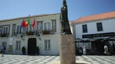 eu : Cascais, Portugal - August 6, 2017: King Peter I Statues in Outubro Square, historic Cascais center, the most popular holiday destination on Lisbon coast.Typical Portuguese mosaic flooring. Blue sky. Stock Footage