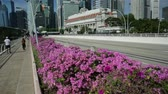 fullerton : Singapore - April 28, 2018: Singapore downtown skyline with Fullerton Hotel, skyscrapers Business District, Esplanade Bridge and people walking in Marina Bay Promenade. Sunny day with blue sky.