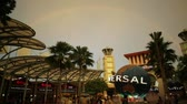 bull ring : Singapore - May 2, 2018: rainbow after a thunderstorm in Sentosa at sunset. Universal Studios moving globe in Bull Ring square on background. Universal Studios first Hollywood movie theme park in Asia