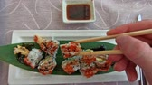 взял : SLOW MOTION: chopsticks picking Uramaki of shrimp tempura, cheese, avocado and tobiko caviar dipped in soy sauce bowl. Japanese fusion food, Asian cultures. Healthy food, light diet concept.