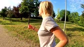 tonificado : SLOW MOTION side view of a healthy woman in sportswear running in the park at sunset. Cardio jogging workout girl training outdoor. Healthy life concept. Stock Footage