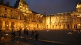 french culture : Paris, France - July 1, 2017: Facade of Louvre Art Museum in Cour Napoleon illuminated at evening. The Louvre Museum is one of the worlds largest museums. Famous landmark in Paris Capital. Stock Footage