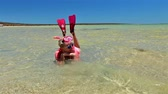 pêssego : Caucasian young woman with snorkeling wetsuit, mask and fins in pink and peach color, sunbathing in the tropical natural pool of Little Lagoon in Shark Bay, Denham, Western Australia. Copy space. Vídeos