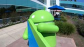caído : Mountain View, California, United States - August 13, 2018: Google Play Android Nougat statue on foreground at Charleston Campus of Google Headquarters in Silicon Valley near Googleplex. Building 47. Stock Footage