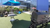 google campus : Mountain View, California, USA - August 13, 2018: Google headquarters relax area with chairs tables and BBQ grill. Stock Footage