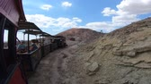 caído : Calico, California, United States - August 15, 2018: Calico train runs a tourist trip through old mines of Calico Ghost Town on Calico Mountains. Stock Footage
