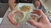 yemek takımı : SLOW MOTION: two white wine glasses doing cheers with hands and celebrate in a restaurant, set table background and slow motion effect. Stok Video
