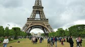 parisiense : Paris, France - July 1, 2017: many people on Champ de Mars looking the Tour Eiffel, icon and symbol of Paris. Cloudy sky in a summer day. Europe travel concept. Stock Footage