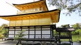 quioto : Kinkaku-ji, the Golden Pavilion, the Zen Buddhist temple, reflects in the lake surrounded by a scenic park. The Rokuon-jii is one of Kyotos most important temples and Unesco heritage. Vídeos