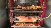 bbq ribs : Close Up of a rotisserie chicken and pork cooking in a typical street restaurant in a Parisian touristic road in Paris, France. Stock Footage