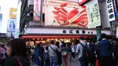 dotonbori : Osaka, Japan - April 29, 2017: crowd of people for Golden Week in Dotonbori area with Kani Doraku crab sign of popular Japanese restaurant. Namba District, nightlife scene.
