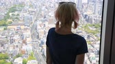 mirador : Aerial view of Osaka skyline in Japan. Young caucasian tourist woman looking Osaka cityscape from the observation deck. Travel and tourism asia concept.