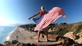 gözcü : Freedom and patriotic concept. Woman holding an American flag waving in SLOW MOTION from Point Dume promontory on Malibu coast in CA, United States. Caucasian female in California West Coast.