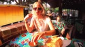 enchilada : SLOW MOTION: El Pueblo de Los Angeles State Historic Landmark, California, United States. Happy tourist woman eating typical Mexican Nachos chips. Oldest part of Downtown