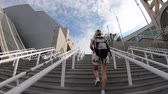 バックパッキング : tourist backpacker woman walking on the stairs of San Diego center at twilight located in Marina district near Gaslamp Quarter. San Diego Downtown, Califonia, Unites States.