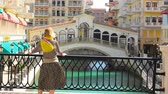 venise : Blonde woman on balcony looking canals of Venice in Doha Qatar. Caucasian tourist enjoys Qanat Quartier in the Pearl-Qatar, Persian Gulf, Middle East, Persian Gulf. Sunny day with blue sky.