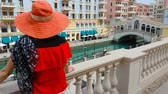 arabistan : Woman on balcony looking at famous bridge reflecting on waters of canals in Venice Doha city. Caucasian tourist at Qanat Quartier in the Pearl-Qatar, Persian Gulf, Middle East. Tourism in Qatar.