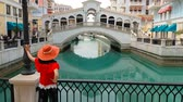 arabistan : Woman standing on balcony looking famous bridge of Venice, Doha Qatar, at twilight. Caucasian tourist at Qanat Quartier in the Pearl-Qatar, Persian Gulf, Middle East. Travel in Arabian Peninsula.