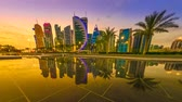 oeste : TIME LAPSE: Scenary of Doha West Bay skyline at sunset to night, reflecting in the water of park in Downtown. Modern glassed skyscrapers of Doha skyline in Qatar, Middle East, Arabian Peninsula. Vídeos