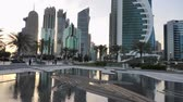 refletindo : Doha, Qatar - February 18, 2019:Scenary of Doha West Bay skyline at sunset reflecting in the water. Modern glassed skyscrapers of Doha skyline in Qatar, Middle East, Arabian Peninsula in Persian Gulf. Stock Footage