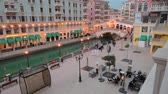 Doha, Qatar - February 20, 2019:Wide angle view of Venetian Rialto bridge replica on canals of luxurious district of Doha illuminated at evening.Panorama of Venice at Qanat Quartier, the Pearl-Qatar.