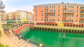 Doha, Qatar - February 20, 2019:TIME LAPSE Wide view of panoramic bridge in Venice at Qanat Quartier in the Pearl, Persian Gulf, Middle East. Aerial picturesque district icon of Doha in venetian style