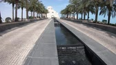 mia : Doha, Qatar - February 16, 2019: MIA park with palm trees and water feature of Museum of Islamic Art in Doha city near Corniche and Dohas Waterfront. Middle East, Persian Gulf. Sunny blue sky. Stock Footage