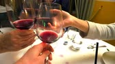 Close up of four hands with red wine glasses while doing cheers to celebrate in a restaurant, set table blurred on background.