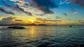 La Digue island of Seychelles, ferry harbour at sunset with boats and Praslin island on background. TIME LAPSE in a sunny cloudy sky at sunset. 動画素材