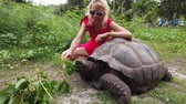 Happy caucasian lifestyle tourist woman on bicycle near Anse Banane in La Digue, Seychelles, with Aldabra Giant Tortoise, Aldabrachelys gigantea. Popular tourist attraction.