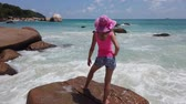 Carefree woman in pink enjoying at Anse Lazio, Praslin Island, Seychelles. Lifestyle female in sunhat on one of Praslins most popular beaches: white sand, granite stones and crystal clear sea.