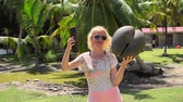 Happy fanny tourist woman holding Lodoicea Maldivica nut male and female, known as coco de mer or sea coconut at Curieuse Island in Seychelles. The coco de mer is endemic to Praslin and Curieuse.
