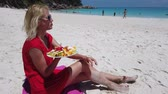 Attractive woman in red dress eats fresh fruit dish at Anse Georgette, Praslin with turquoise sea on background. Lifestyle female enjoy on tropical beach at Seychelles. Healthy exotic summer diet.