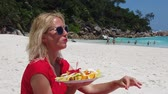 SLOW MOTION: Healthy exotic summer diet. Attractive woman in red dress holding fresh fruit dish at Anse Georgette, Praslin with turquoise sea and palm trees. Happy lifestyle female at Seychelles.