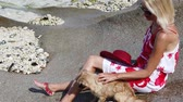 granit : SLOW MOTION: close up of Elegant lifestyle tourist woman and a dog sitting on big boulders. Crystal sea and granite rocks at Anse Source dArgent one of most beautiful beaches in La Digue, Seychelles.