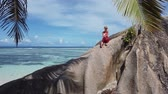 fonte : Summer in La Digue, Seychelle. Carefree tourist woman with red hat sitting on a huge granite boulder at Anse Source dArgent. Female lifestyle above big rocks with turquoise sea and palm leaves.