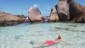 swimming natural pool, La Digue, Anse Marron. Tourist girl in orange bikini enjoying clear waters of Anse Marron, Seychelles, protected by huge rock formations