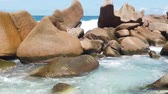 SLOW MOTION: Swimming pool Anse Marrone, La Digue. Happy woman in bikini lying on turquoise water of natural pool at Anse Marron by rock formations. Scenic landscape of secret beach at Seychelles. 動画素材