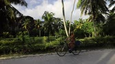 SLOW MOTION: La Digue, Seychelles. Tourist woman on bicycle pointed Giant Union Rock in palm trees grove at Union Estate, a former coconut and vanilla plantation near Anse Source dArgent.