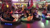 atlıkarınca : Province of Bologna, Italy - June 8, 2019: Children and young people playing driving wild bumper cars, in the Amusement Park night arena and crashing each other. Cars with European contries flags. Stok Video