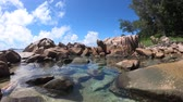 pedregulho : woman in bikini lying in natural pool in La Digue, Seychelles. Turquoise calm waters of swimming pools at Anse Caiman remote beach between Anse Fourmis and Anse Cocos protected by huge rock formations Vídeos