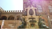 touristic place : Bologna, Italy - June 24, 2019: sun rays on Neptune 1500s bronze statue fountain with San Petronio gothic basilica and cathedral, built between the 1400s and 1600s in Piazza Maggiore square. Stock Footage